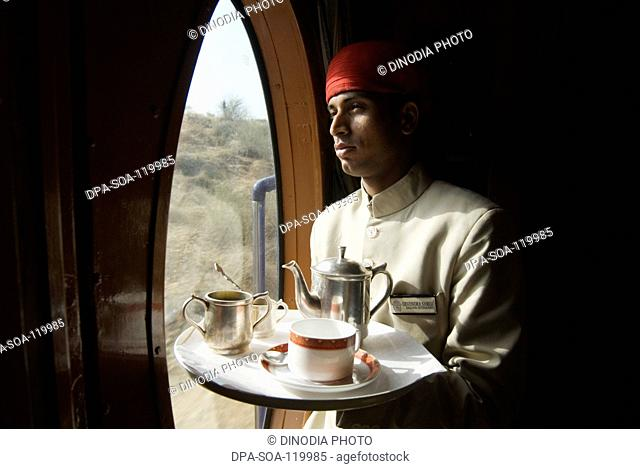 Rajasthani attendant holding tray of  beverage in Heritage on Wheels Journey into Past luxury tourist train ; Rajasthan ; India