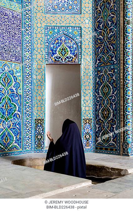 Woman wearing robe praying at mosque