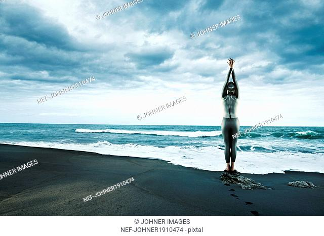 MI adult woman n wetsuit at beach