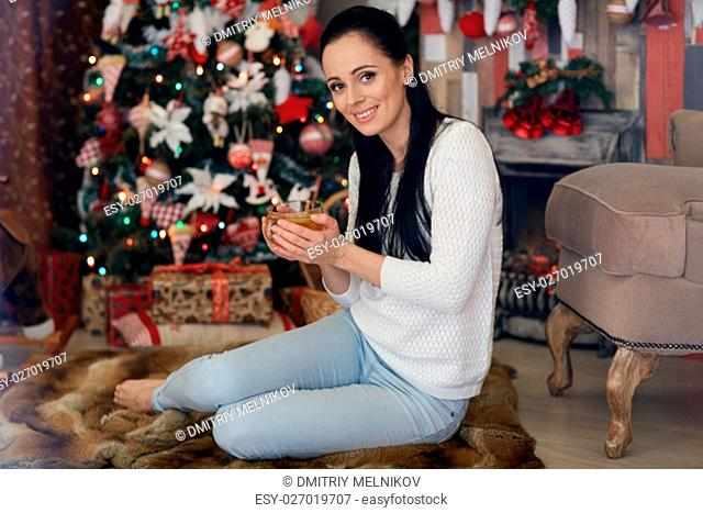 Young happy beautiful woman with cup of tea sits near Christmas tree in the room of the house. Merry Christmas and New Year