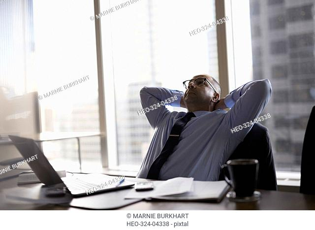 Tired male lawyer with hands behind head in conference room