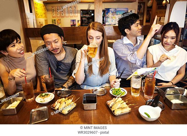 Five people sitting sidy by side at a table in a restaurant, eating and drinking beer