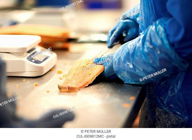 Man in smokehouse filleting salmon