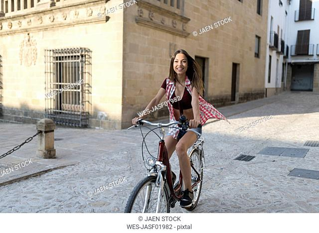 Spain, Baeza, smiling young woman riding bicycle in the city