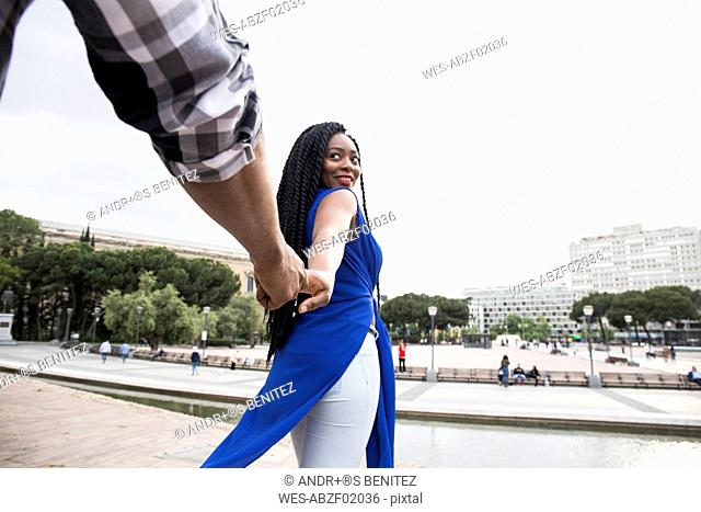 Spain, Madrid, portrait of smiling young woman holding hand with her partner