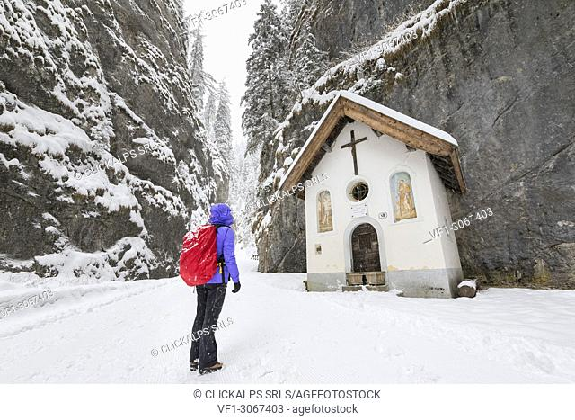A girl is looking the small Church inside the Sottoguda Serrai Gorge at the foot of Marmolada (Sottoguda, Rocca Pietore, Belluno province, Veneto, Italy