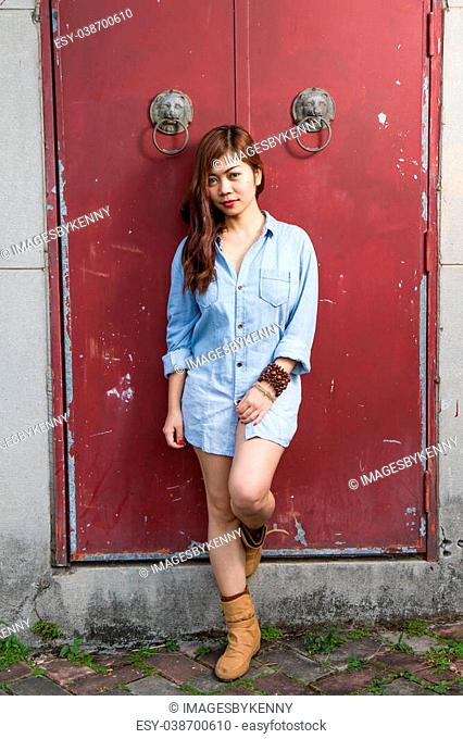 Asian woman in front of traditional Chinese door with ornate lion head knockers