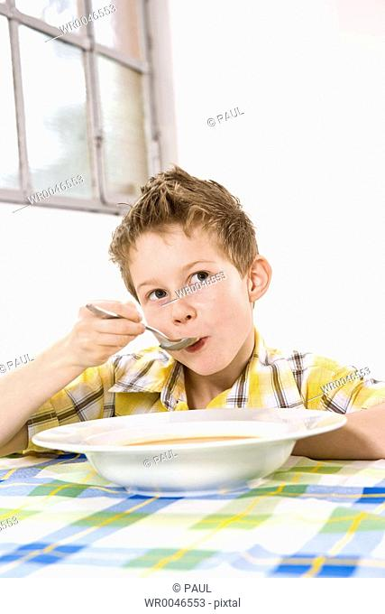 Boy having soup and thinking