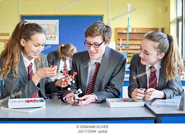 High school students assembling molecule model in science class