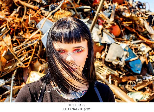 Portrait of woman in scrap yard looking at camera