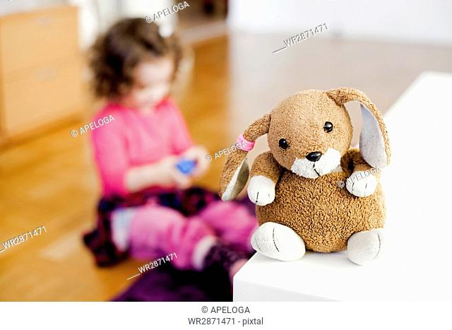 Close-up of stuffed toy on table with girl playing at home