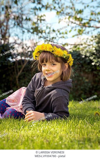 Portrait of smiling little girl lying on meadow wearing floral wreath of dandelions