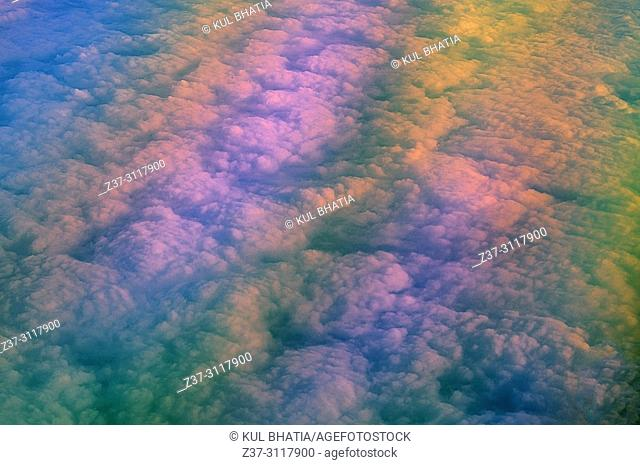 Aerial view of clouds below, at 10,000 meters, photographed from a regular commercial flight