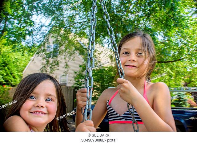Portrait of two cute sisters playing on swing in garden
