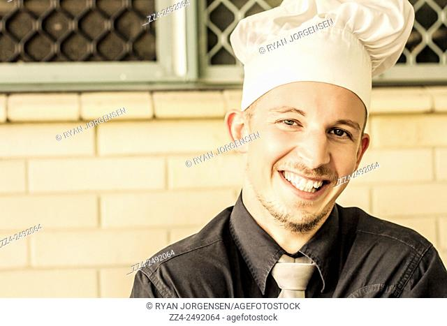 Headshot of a restaurant owner smiling in chef hat outside store shopfront. Small business owners