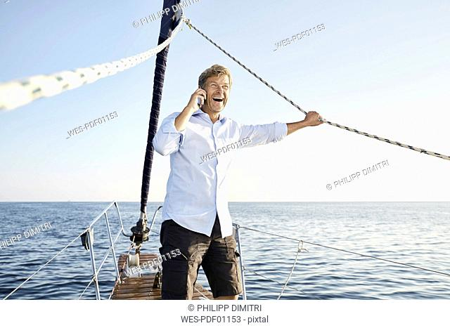 Laughing mature man on the phone on his sailing boat