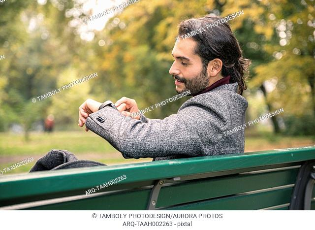 Male Hispanic businessman using smartwatch on bench in park