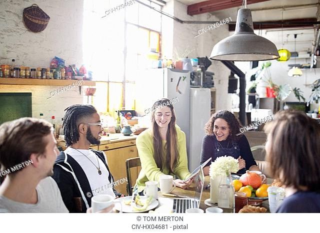 Young adult roommate friends using digital tablet and laptop at breakfast table in apartment