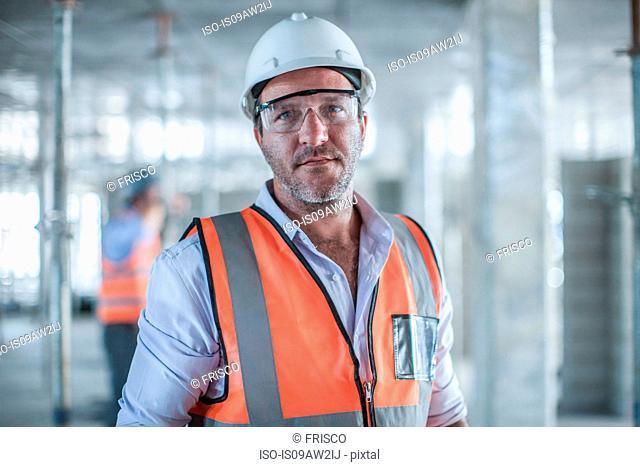 Portrait of mid adult male site manager on construction site