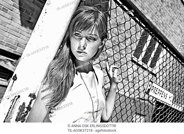 Teen female in summer clothing standing casually against a wire fence