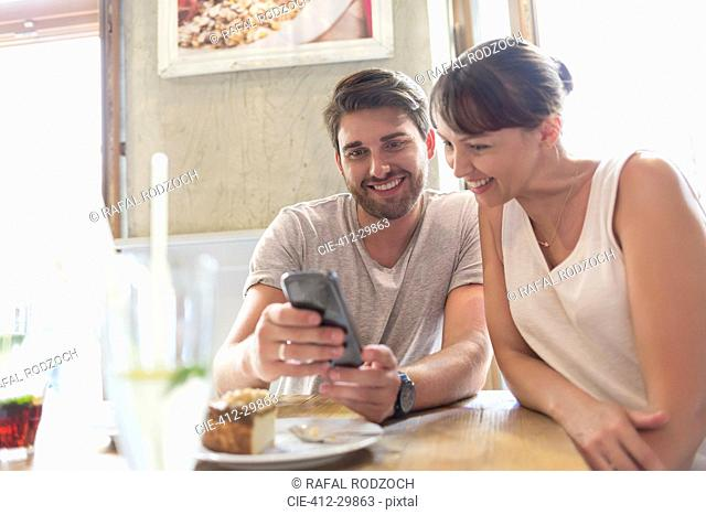Couple texting with cell phone at cafe table