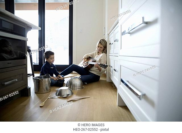 Mother playing guitar and son banging kitchen pots