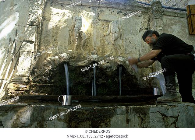 Side profile of a mature man filling a jug with water from a drinking fountain, Crete, Greece