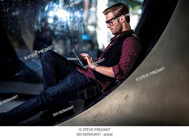 Young businessman reclining on curved wall reading digital tablet touchscreen