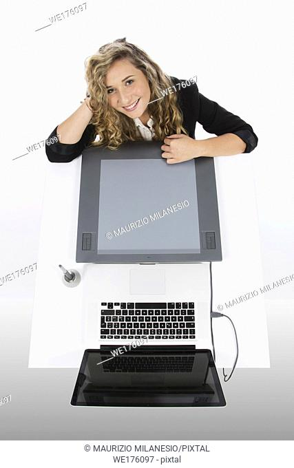 Graphic designer seen from above with a tablet and a laptop, she is smiling and with her arms resting on the desk and her head