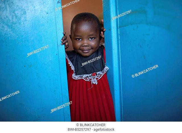 little girl in a red cloth looking out of a blue door, Burundi, Bujumbura Mairie, Bujumbura