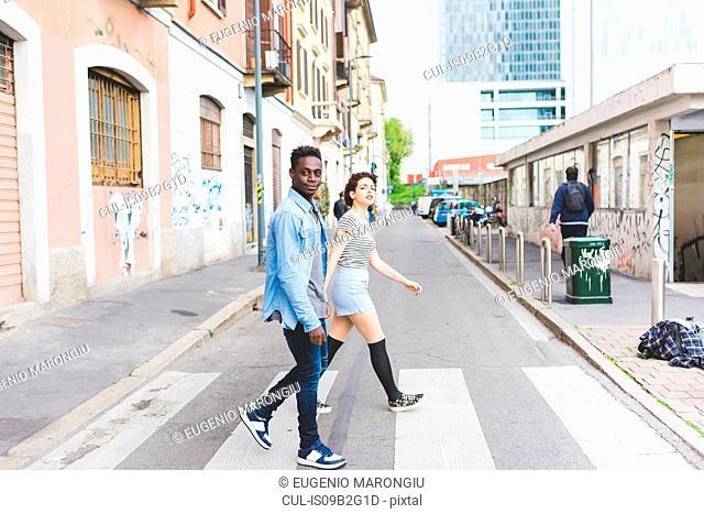 Couple walking across pedestrian crossing, Milan, Italy