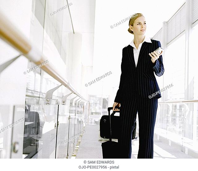 Businesswoman with luggage and blackberry