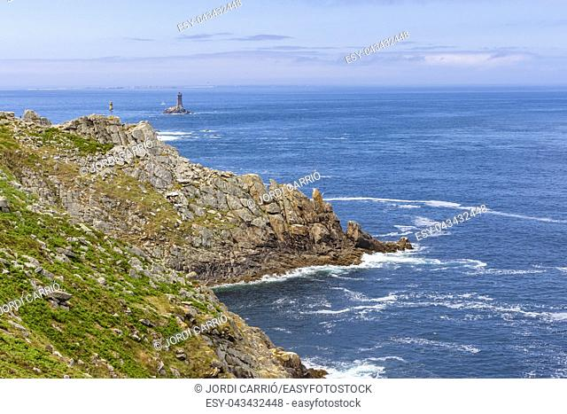 View from the tip of Cape Raz, the strait of Sein Island with the old lighthouse in the background in the French Brittany