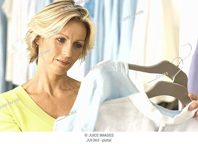 Mature woman shopping in clothes shop, comparing two tops on coathangers, close-up