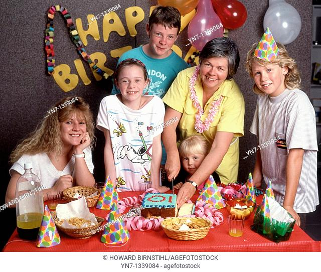 Happy family groups at ten year-old's birthday party posing for the camera