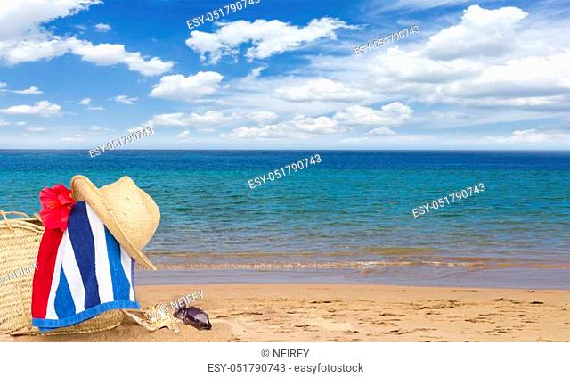 beach towel and hat on sandy beach in straw bag banner, summer relaxation and vacations concept