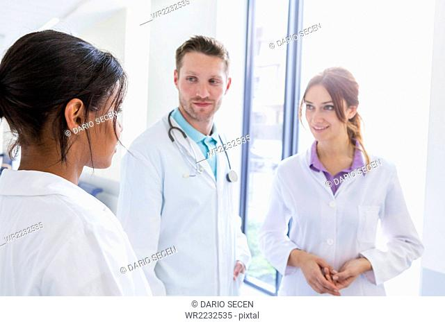Doctor and coworkers talking in hospital corridor