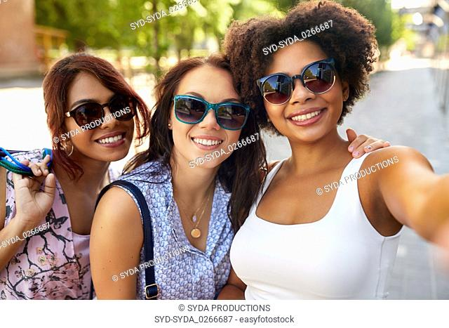 happy young women in sunglasses at summer park