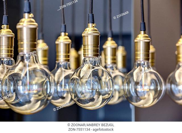 Edison lamps suspended from the ceiling in a regular geometric sequence. One lamp in focus. The rest of the optical out of focus