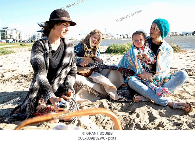 Sisters and their children enjoying beach