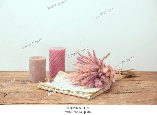 Candles, bunch of dry flowers and clipped book