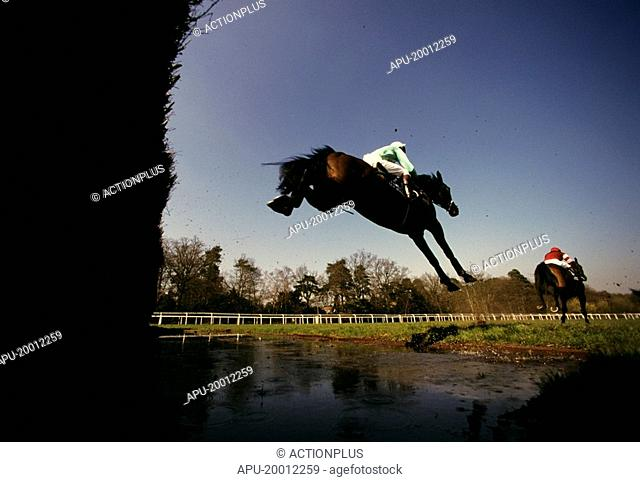 Below fence view as steeplechasing horses clear water jump fence