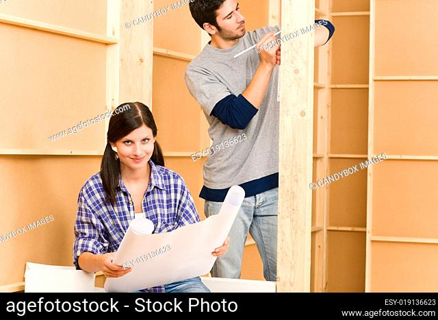 Home improvement young couple with blueprints