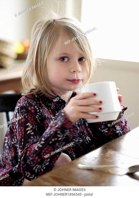 Girl sitting at kitchen table and looking at camera