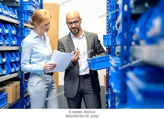 Businessman and businesswoman examining workpiece in factory storehouse