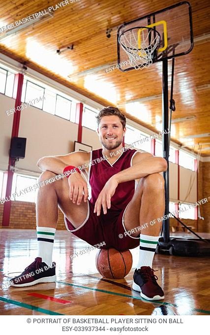 Portrait of basketball player sitting on ball against hoop in court