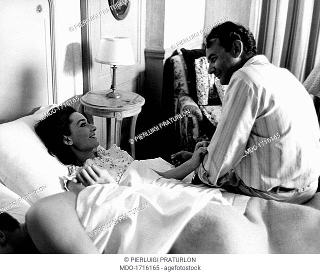 American director Stanley Donen, sit on the side of a bed, talk affectionately with Audrey Hepburn, under the blankets in a dressing gown