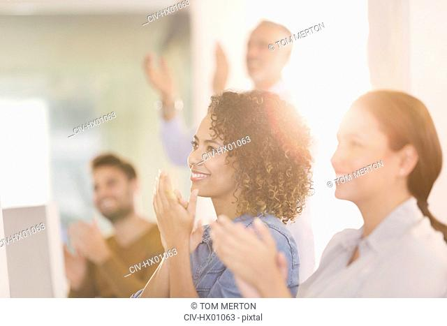 Businesswomen clapping in office