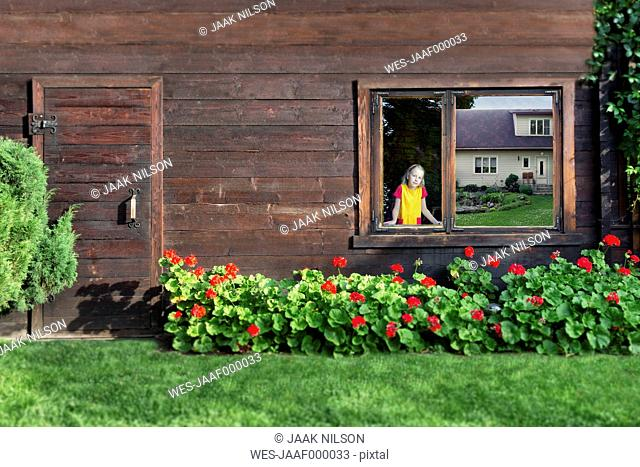 Estonia, girl looking through window of a log cabin