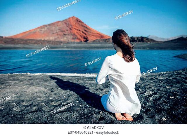 Back view of woman in white clothes praying in unique black sand beach Playa Bermeja, Lanzarote, Canary Islands, Spain. Lake and mountain on background